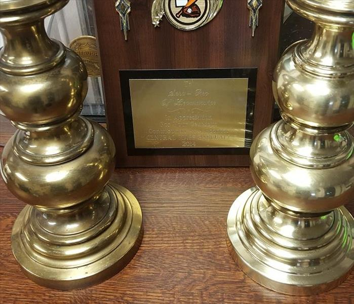 Before and after of smoke and soot damaged brass candlesticks.  One has been cleaned, the other has not